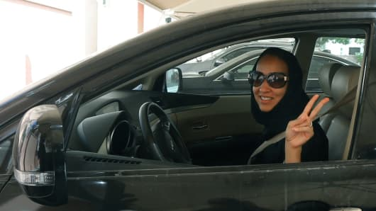 Saudi activist Manal Al Sharif, who now lives in Dubai, flashes the sign for victory as she drives her car in the Gulf Emirate city