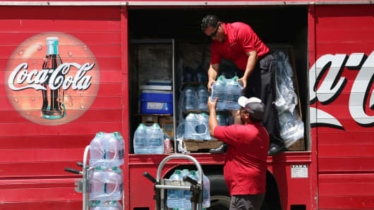 Employees deliver Coca-Cola Co. Dasani brand water bottles to a convenience store in the Miramar neighborhood of San Juan, Puerto Rico, on Friday, Sept. 29, 2017.
