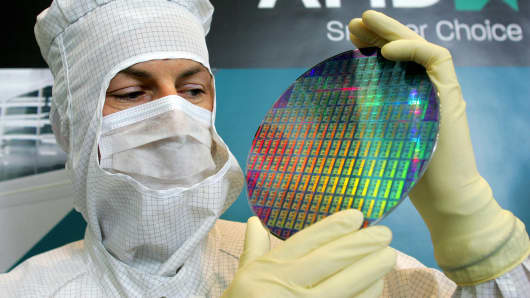 A worker holding a wafer at Advanced Micro Devices