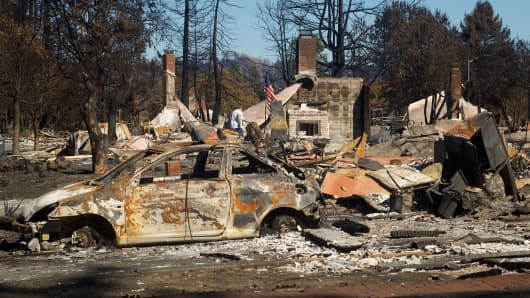 The charred remains of a vehicle sits in scorched neighborhood in Santa Rosa, California after wildfires swept the area.