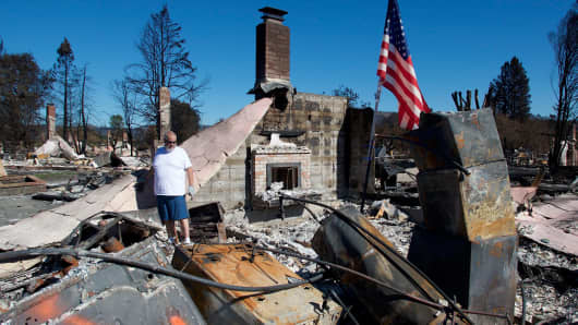 A resident searches through the debris after wildfires destroyed his home in Santa Rosa, Calif.