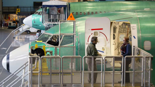 Employees on a platform next to a Boeing 737 MAX 9 jetliner at the company's manufacturing facility in Renton, Washington.