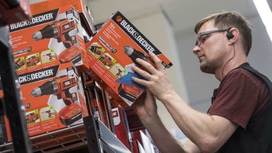 A worker stocks a shelf with Stanley Black & Decker power drills.
