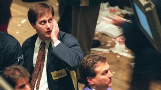 A trader on the floor of the New York Stock Exchange watches the board as trading is halted and the market closed, down 554.26 points, 27 October, in New York. Blue chip stocks recorded their biggest-ever points fall as Wall Street staggered under the Asian financial crisis.