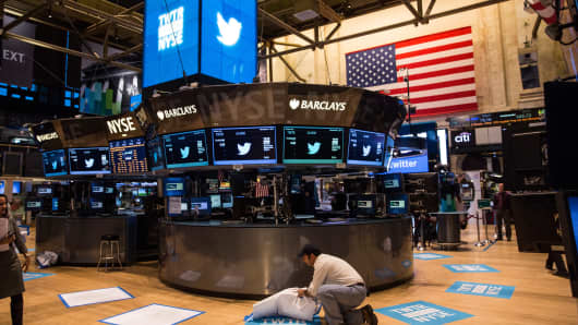 A worker unveils a floor mat bearing the logo of Twitter and the symbol on which Twitter's stock will traded (TWTR) on the floor of the New York Stock Exchange (NYSE) on November 7, 2013 in New York City.