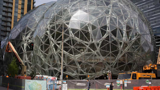 People walk past the signature glass spheres under construction at the Amazon corporate headquarters on June 16, 2017 in Seattle.