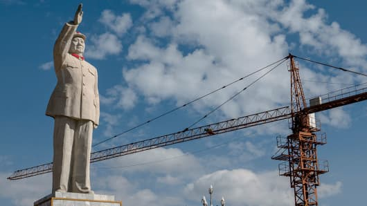 Construction cranes work beside the statue of Mao Zedong in Yunnan Province, China.