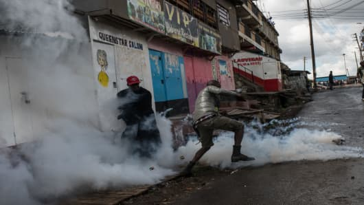 A tear gas canister explodes in front of two National Super Alliance protesters inside Mathare slum in Nairobi, Kenya, on October 26, 2017.