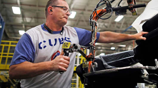 A worker uses a hoist to assemble a car seat at the Lear Corp. manufacturing facility in Hammond, Indiana.