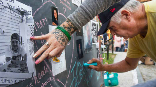 Tim Talbot Sr. of Portland, Maine writes on the memory board in honor of his son Timothy Jr during an Overdose Awareness vigil at Monument Square in Portland, August 31, 2017. The Talbots lost their son, who was 41, to an overdose laced with fentanyl.