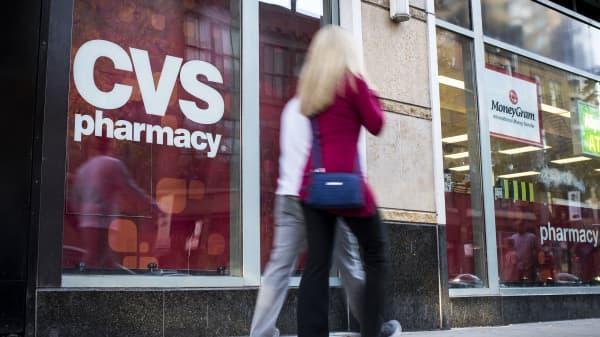 Pedestrians walk past a CVS Health Corp. store in Chicago.