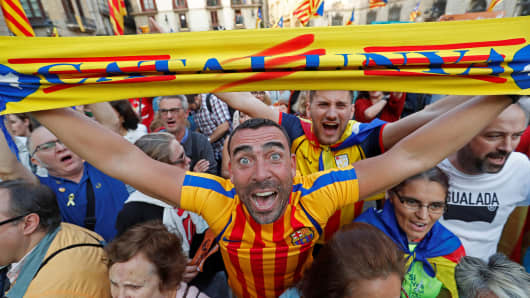 A man displays a scarf featuring an Estelada (Catalan separatist flag) design, as he reacts at Sant Jaume Square after the Catalan regional parliament declares independence from Spain in Barcelona, Spain October 27, 2017.