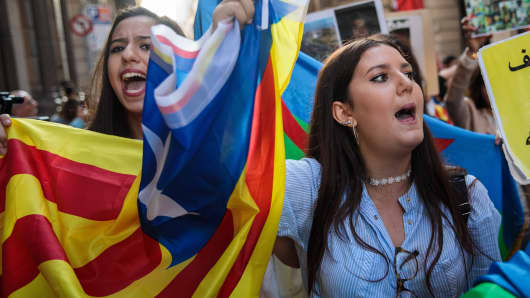 Moroccan Rif activists carry a Catalan independence flag during a demonstration outside the Catalan Government building, the Palau de la Generalitat on October 28, 2017 in Barcelona, Spain. The Spanish government stripped Catalonia of its autonomy after the Catalan parliament voted yesterday to declare independence.
