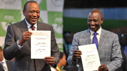 Kenya's President-elect Uhuru Kenyatta (L) and his running mate William Ruto hold up certificates of election October 30, 2017.