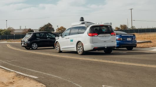 A Waymo self-driving van encounters two stalled cars in a staged scenario in the company's testing ground.