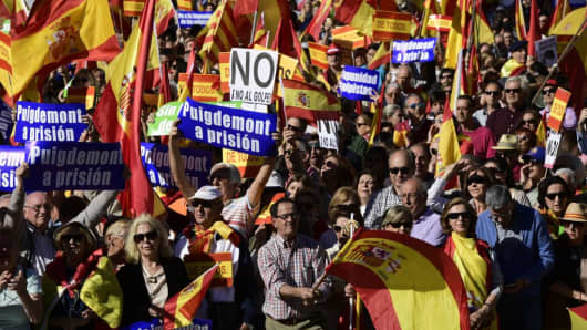 People hold signs reading 'No to the impunity of coup plotters' and '(Catalan regional president Carles) Puigdemont to prison' while waving Spanish flags during a demonstration calling for unity at Plaza de Colon in Madrid on October 28, 2017