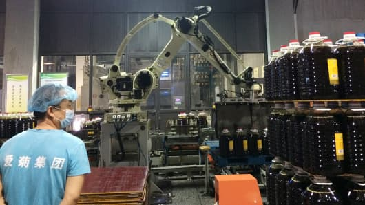 Two workers at Xi'an Aiju Grain and Oil Industry Group monitor a robot as it handles jugs of rapeseed oil.