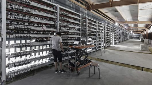 A technician inspects bitcoin mining machines at a mining facility operated by Bitmain Technologies Ltd. in Ordos, Inner Mongolia, China, on Friday, Aug. 11, 2017.