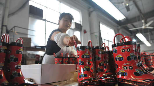 A woman works in a Macintosh boot factory in Lin'an, located in the east China province of Zhejiang.