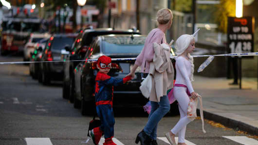 Kids in Halloween Customscross the street near the scene where a man driving a rental truck struck and killed eight people on a jogging and bike path in Lower Manhattan on October 31, 2017 in New York City.