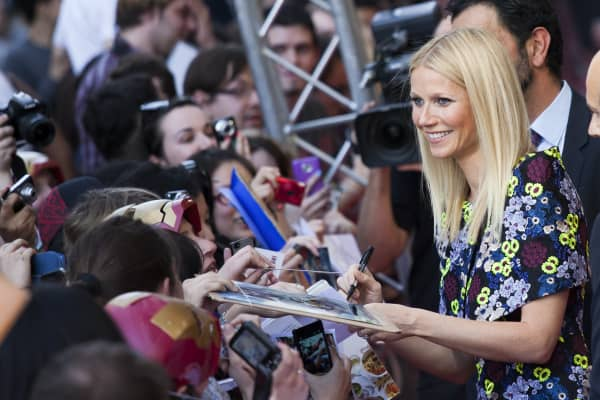 Gwyneth Paltrow (R) signs autographs for fans as she arrives to the premiere of 'Iron Man 3' at Le Grand Rex on April 11, 2013 in Paris, France.