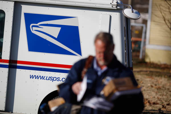 A United States Postal Service (USPS) letter carrier delivers mail in Shelbyville, Kentucky.