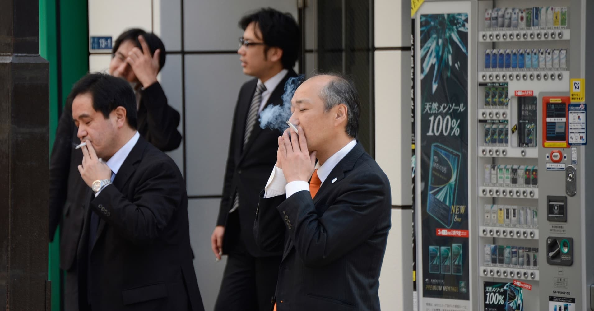 Businessmen smoke cigarettes in Tokyo on March 13, 2013.