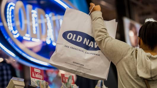 A customer lifts a shopping bag at an Old Navy Inc. store in San Francisco.