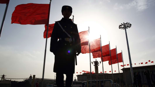 A paramilitary police officer stands guard in front of red flags at Tiananmen Square in Beijing, China.