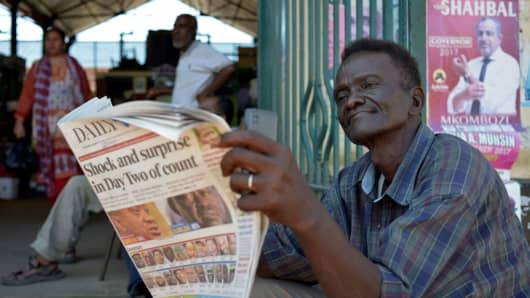 A man reads a newspaper outside the central market in Mombasa, Kenya, on August 10, 2017, as the country waits for the final results from the general election.