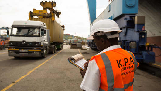 A dock worker for the Kenya Ports Authority monitors the movement of shipping containers unloaded from freight ships in Mombasa, Kenya, on April 26, 2013.