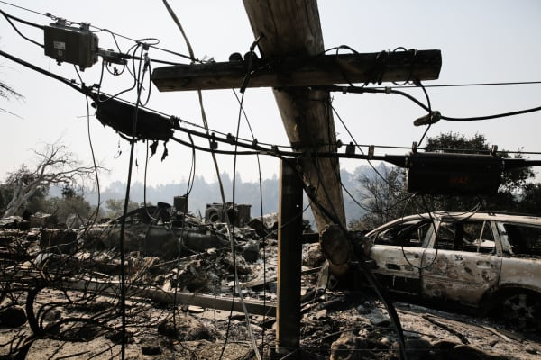 A downed power line and the remains of a home and a car are seen in the Larkfield-Wikiup neighborhood following the damage caused by the Tubbs Fire on October 13, 2017 in Santa Rosa, California.