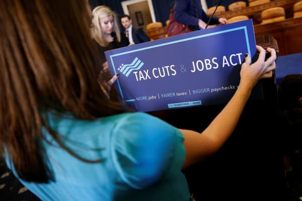 A congressional aide places a placard on a podium for the House Republican's legislation to overhaul the tax code on Capitol Hill in Washington, November 2, 2017.