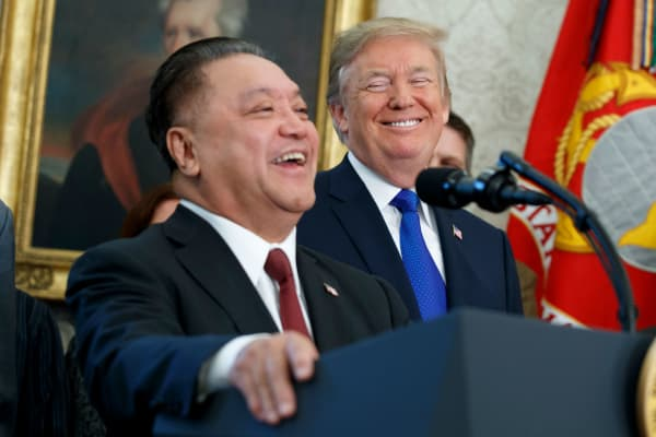 President Donald Trump smiles at Broadcom CEO Hock Tan during an event to announce that the company is moving its global headquarters to the United States, in the Oval Office of the White House, Thursday, Nov. 2, 2017, in Washington.