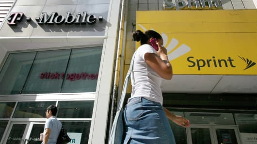 A woman talks on her phone as she walks past T-mobile and Sprint wireless stores in New York.