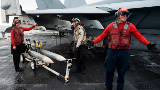 Ordnancemen gesture before loading 'dummy' missiles onto an F/A-18 Hornet on the deck of the USS George H.W. Bush aircraft carrier in the Atlantic ocean on October 25, 2017,