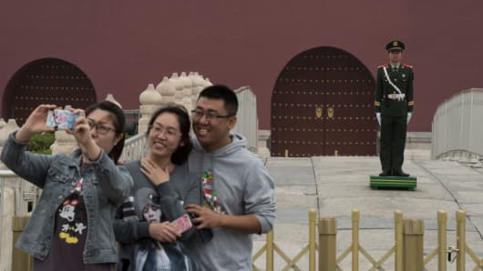 Chinese tourists pose in front of The Forbidden City in Beijing on Oct. 21, 2017.