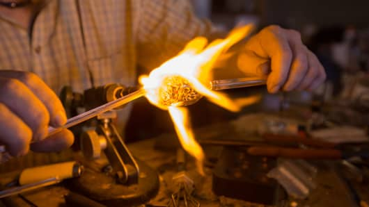 A glassblower working with a torch making small scale pipes and ornaments.