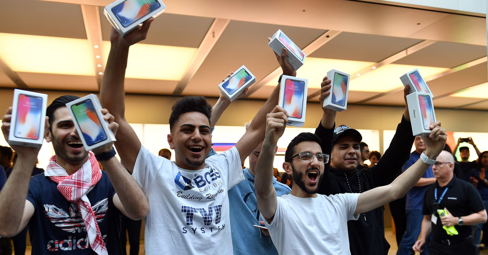 First customers display their iPhone X sets at an Apple showroom in Sydney on November 3, 2017. Apple iPhone X went for sale in Australia with long queues outside the Apple stores.
