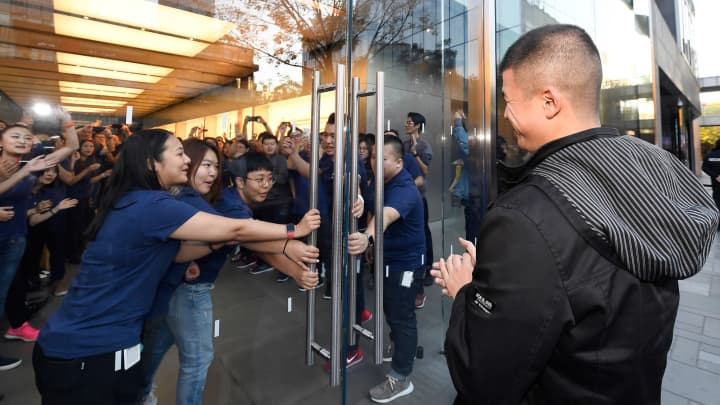 Working staff open the door to welcome Apple fans at the Sanlitun Apple Store on November 3, 2017 in Beijing, China.