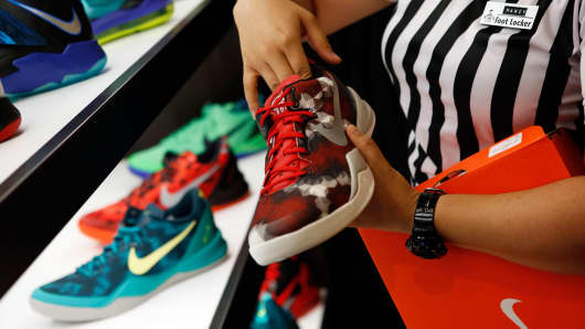 An employee arranges Nike basketball shoes on display at the House Of Hoops by Foot Locker retail store at the Beverly Center in Los Angeles.
