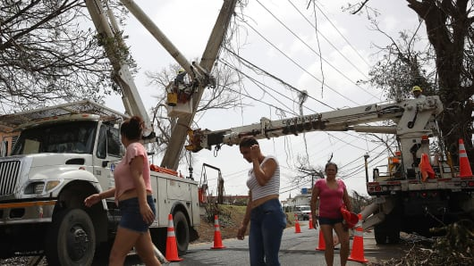 An electrical crew attempts to repair power lines that were knocked over Hurricane Maria passed through on September 27, 2017 in Corozal, Puerto Rico.