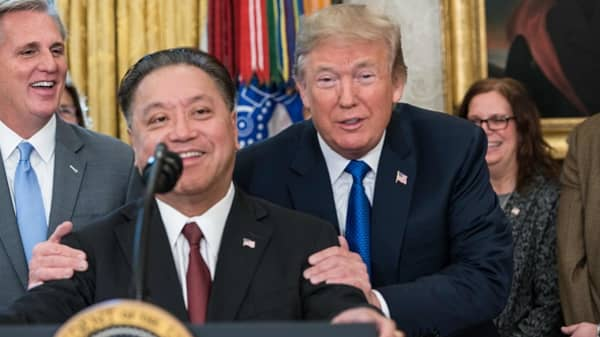 US President Donald Trump jokes with Broadcom CEO Hock Tan as he announces that Broadcom would be moving back to the US in the Oval Office at the White House in Washington, DC, on November 2, 2017