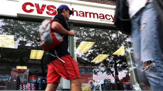 People walk past a CVS store in New York.