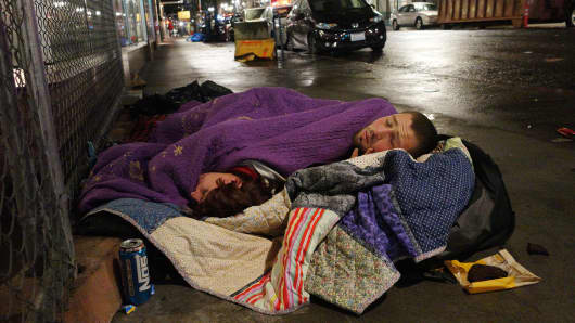 Taz Harrington, right, sleeps with his girlfriend, Melissa Ann Whitehead, on a street in downtown Portland, Ore. Harrington, who is in his 20s, said he met Whitehead, who was already homeless, online and came to Oregon to be with her even though he knew they would be sleeping outside.