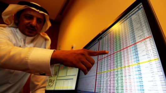 An investor gestures as he monitors a screen displaying stock information in Riyadh, Saudi Arabia, November 6, 2017.