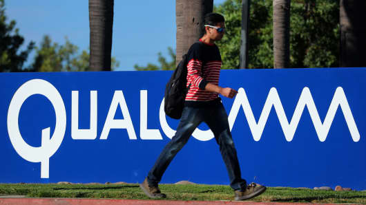 A pedestrian passes a sign on the Qualcomm campus in San Diego, California.