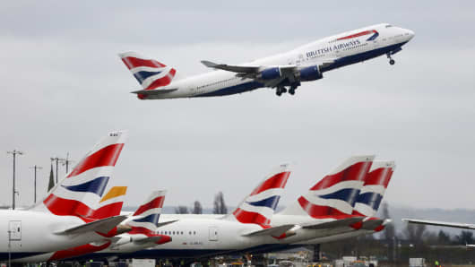 A Boeing Co. 747 passenger aircraft, operated by British Airways, a unit of International Consolidated Airlines Group SA (IAG), takes off over a row of passenger aircraft operated by British Airways at Heathrow airport in London, U.K.