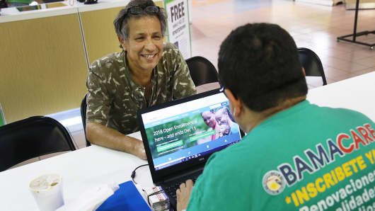 Rudy Figueroa (R), an insurance agent from Sunshine Life and Health Advisors, speaks with Marvin Mojica as he shops for insurance under the Affordable Care Act at a store setup in the Mall of Americas on November 1, 2017 in Miami, Florida.