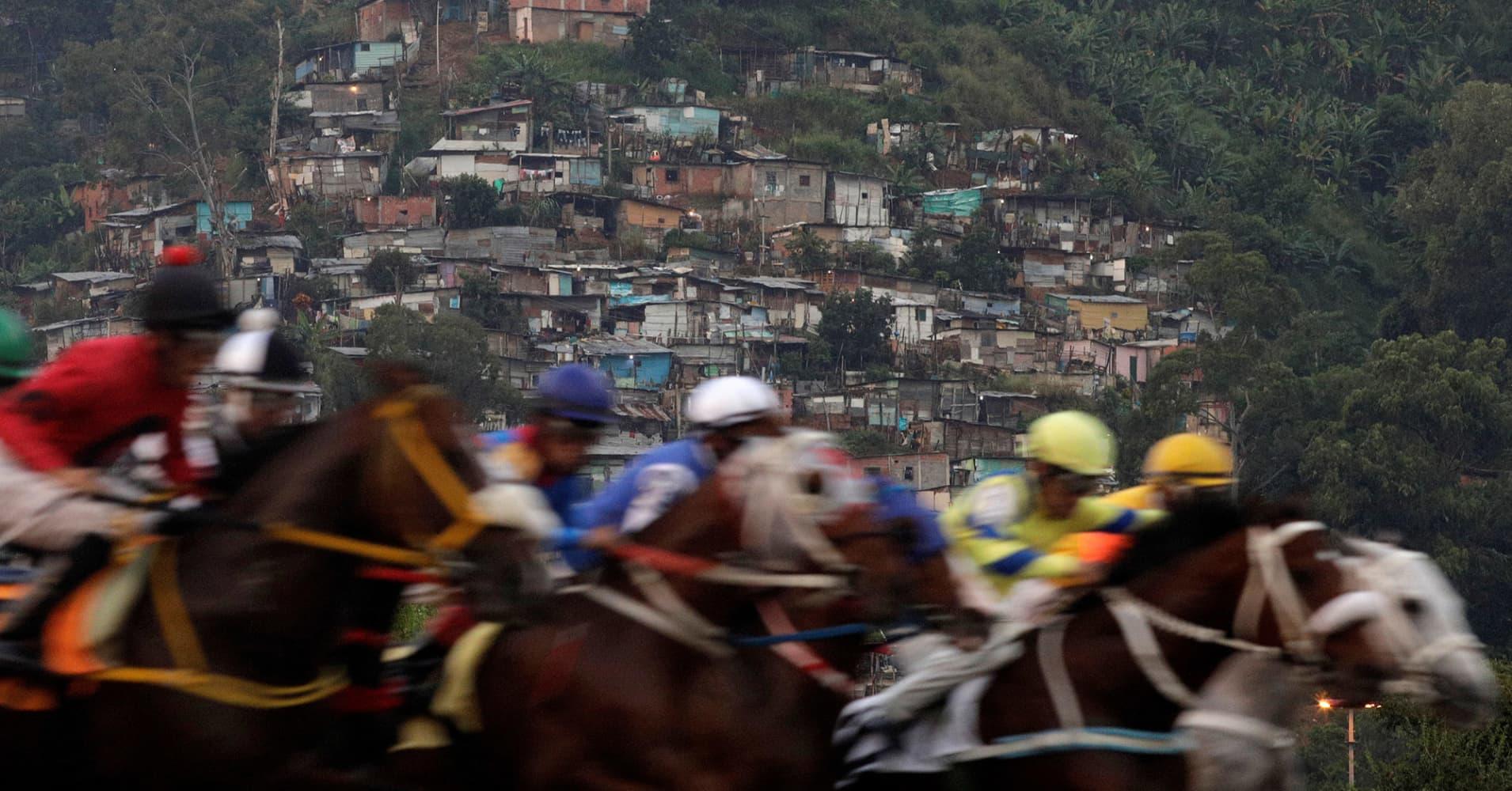"Competitors take part in a horserace, with a slum or ""barrio"" in the background at La Rinconada Hippodrome, Caracas, Venezuela."